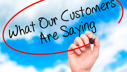 Man Hand writing What Our Customers Are Saying with black marker on visual screen. Business, technology, internet concept.